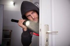 Thief Peeking From Door. Thief With Flashlight And Crowbar Peeking From Door stock photos