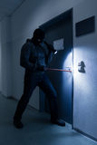 Thief With Flashlight Trying To Break Office Door Royalty Free Stock Photo