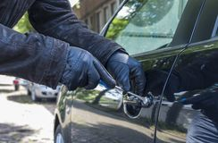 A thief breaks into a car. A thief with hand gloves breaks into a car using a screwdriver royalty free stock images