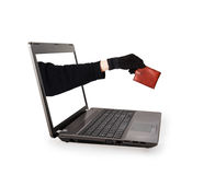 Thief hand with leather purse from a laptop screen Royalty Free Stock Photos