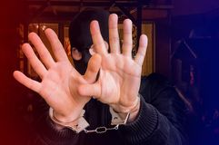 Thief in handcuffs is covering face. Police arrested him near crime scene Royalty Free Stock Images
