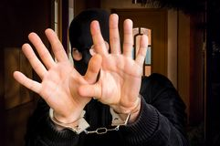 Thief in handcuffs is covering face. Police arrested him near crime scene Royalty Free Stock Photography