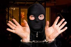 Thief in handcuffs - police arrested him. Near crime scene Stock Photos
