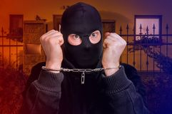 Thief in handcuffs - police arrested him. Near crime scene Stock Image