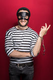 Thief with handcuffs smiling. Portrait on red background Stock Photography