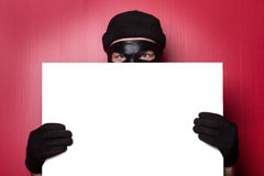 Thief hiding behind advert. And looking Royalty Free Stock Image