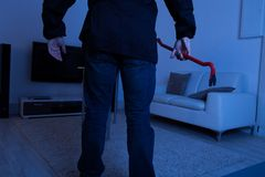 Thief holding crowbar in living room Royalty Free Stock Images
