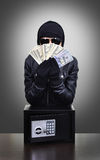 Thief holding dollars. Thief holding a stolen dollars on black background stock photo