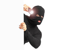 Thief with holding a flashlight behind a white pa Royalty Free Stock Photography