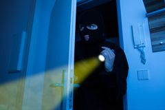 Thief holding flashlight while entering into house. Thief holding flashlight while secretly entering into house Royalty Free Stock Image
