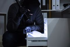Thief Stealing Document From Drawer royalty free stock image