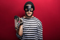 A thief holding stolen necklace. Portrait on red background Royalty Free Stock Images