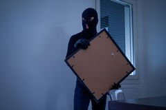 Thief inside home stealing a painting. From the wall stock photo