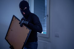 Thief inside home stealing a painting from wall. Thief inside home stealing a painting from the wall royalty free stock images