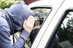 A thief in a jacket with a hood looks into the car through a clo Royalty Free Stock Image