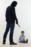 Thief kidnapper with child. Thief Burglar kidnapper threaten the little child with knife during kidnapping Stock Photo