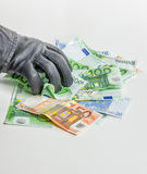 Thief with leather glove is grabbing bills Royalty Free Stock Images