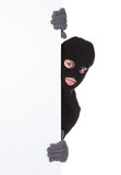 Thief looking around a blank sign. Thief in a balaclava and gloves looking around the edge of a blank sign with copyspace for your text isolated on white Royalty Free Stock Image