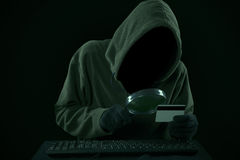 A thief looking at credit card code Stock Photo