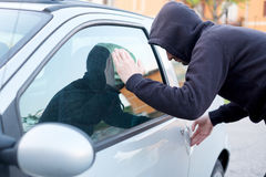 Thief looking inside a car window ready to steal Royalty Free Stock Photos