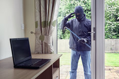 Thief looking through patio doors window at a laptop computer to. Thief breaking into a house via a patio doors window with a crowbar to steal a laptop computer Royalty Free Stock Images