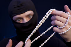 Thief. Man in black mask with a pearl necklace Royalty Free Stock Photography