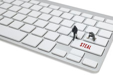Thief man miniature figure concept steal data on keyboard Royalty Free Stock Images