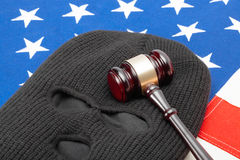 Thief mask with judge gavel over US flag - studio shot Royalty Free Stock Photography