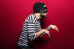 A thief with mask slinking. On red background Stock Photos
