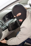 Thief in mask steals car. Royalty Free Stock Image