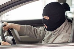 Thief in mask steals car. stock images