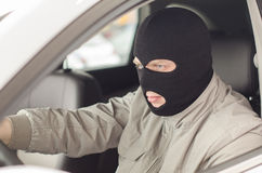 Thief in mask steals car. Royalty Free Stock Photos