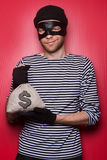 Thief with money bag. Happy thief with money bag. Red background Royalty Free Stock Photography