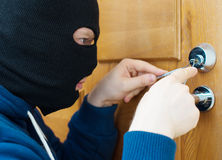 Thief. Thief opening door with lock picker stock photo