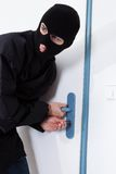 Thief opening door with tool during house breaking. Alert thief looking away while opening door with tool during house breaking Royalty Free Stock Image