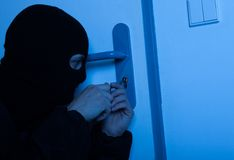 Thief Opening House Door With Tool Royalty Free Stock Image