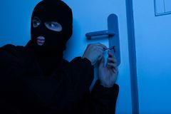 Thief Opening House Door With Tool. Thief in balaclava opening house door with tool Stock Image