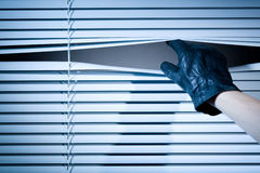 Thief Opening Window Blinds. The hand of a thief wearing a leather glove peeking through a window with closed venetian blinds Royalty Free Stock Images