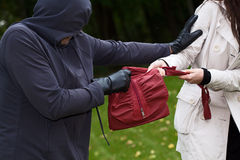 Thief in the park. Agressive thief in the park snatching a purse Royalty Free Stock Photo