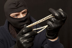 Thief with a pearl necklace Stock Photography