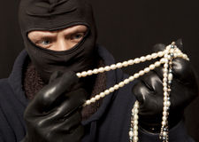 Thief with a pearl necklace Stock Photo