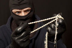 Thief with a pearl necklace Royalty Free Stock Photo