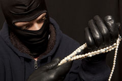 Thief with a pearl necklace Stock Photos