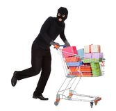 Thief pushing a trolley of gifts Royalty Free Stock Image