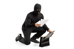 A thief reading a confidential documents. After stealing a briefcase  on white background Royalty Free Stock Images