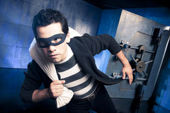 Thief running away with money. Thief running out of a bank vault, low-key photo Stock Photos