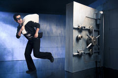 Thief running away with money. Thief running out of a bank vault, low-key photo Stock Images