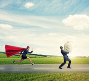 Thief running away from superwoman Royalty Free Stock Image