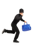 Thief running with a purse and finger on lips. Full length portrait of a thief running with a stolen purse and finger on lips gesturing silence isolated on white Stock Images