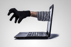 Thief's  hand reach out of computer. Identity theft concept with hand reach out of computer isolated on grey Royalty Free Stock Image